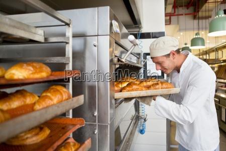 sorridente panettiere controllo vassoio di pane