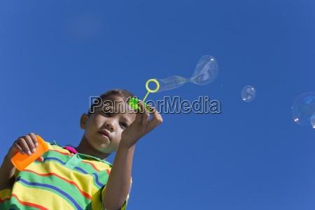 ragazzo che soffia bolle con bolle