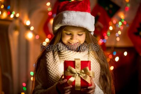 bambina guardando scatola aperta con regalo