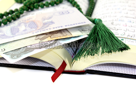 open koran with egyptian currency