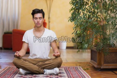 giovane uomo meditando sul suo pavimento