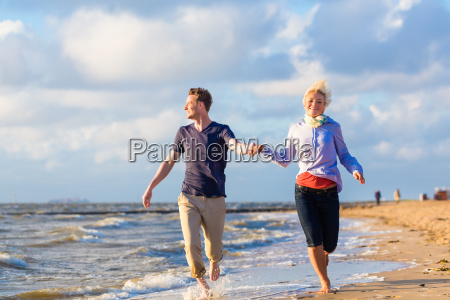 couple running through waves and sand