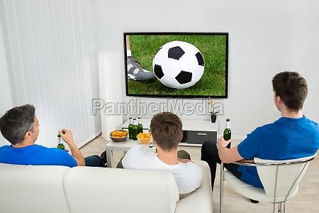 tre uomini che guardano la partita