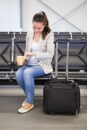 businesswoman check time alla lobby dellaeroporto