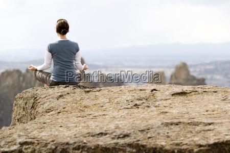 una donna che medita sul bordo