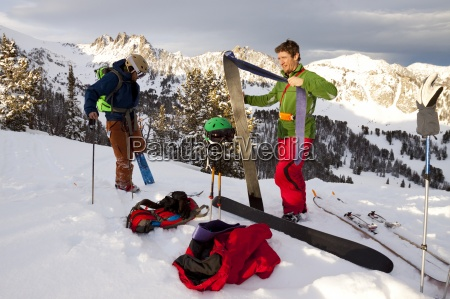 two fit male backcountry skiers pull