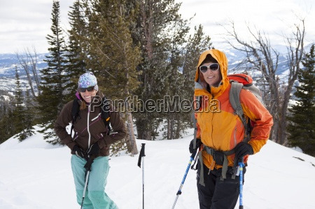 two female backcountry skiers pause on