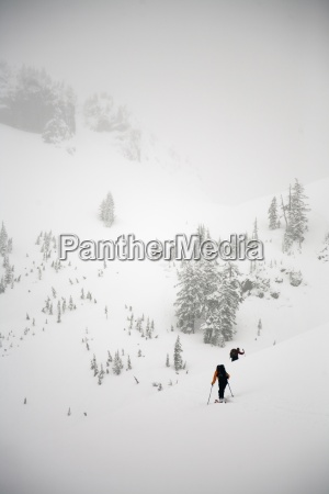 two female backcountry skiers skin up