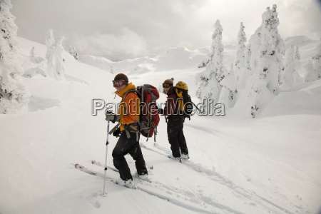two female backcountry skiers surveys the