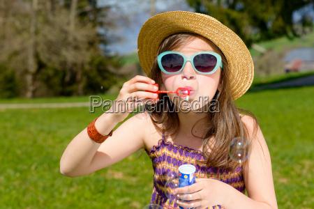 una bambina che fa bolle di