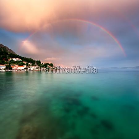 arcobaleno sopra la spiaggia rocciosa e