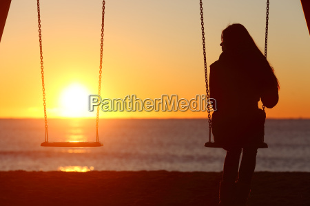 donna zitella sola oscillazione sulla spiaggia