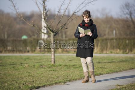 donna a piedi e lato lettura