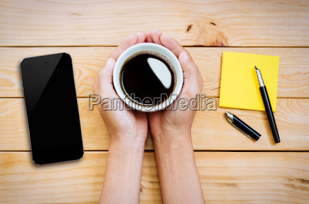hand holding coffee cup with smartphone