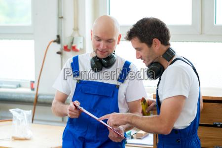 capo e lavoratore in una falegnameria