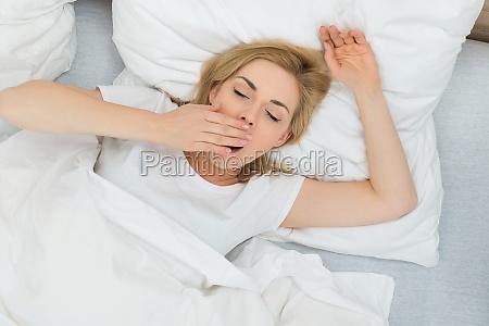 donna sbadiglio in camera da letto