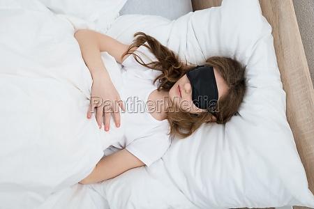 girl sleeping on bed with sleep