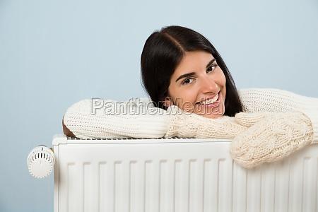 donna in maglione appoggiato sul radiatore