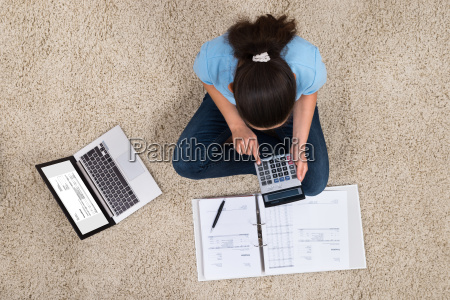 woman calculating invoices at home