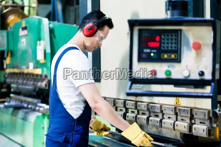 operatore di macchina asiatico in impianto