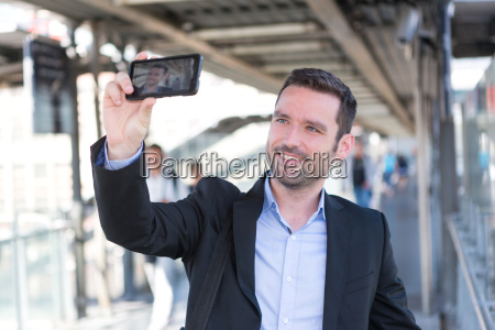 young attractive businessman taking some selfies