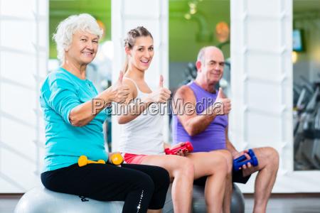 anziani ed addestratori con i dumbbells