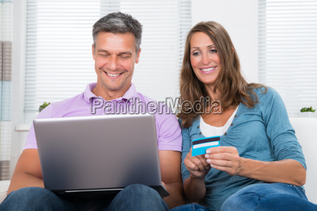 mature couple shopping online on laptop