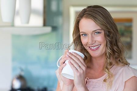 bella bionda che tiene una tazza