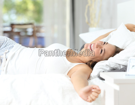ragazza svegliarsi stretching armi sul letto