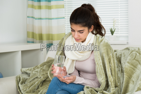 sick woman covered with blanket holding