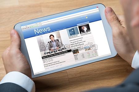 imprenditore che legge notizie sul tablet