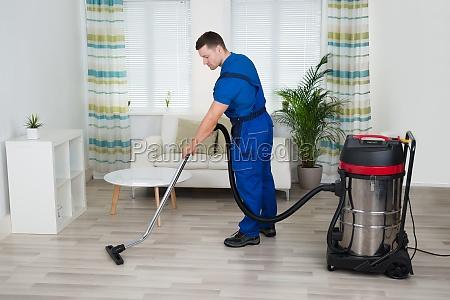 lavoratore pulizia pavimento con pulitore a
