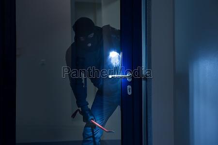ladro con la torcia elettrica cercando