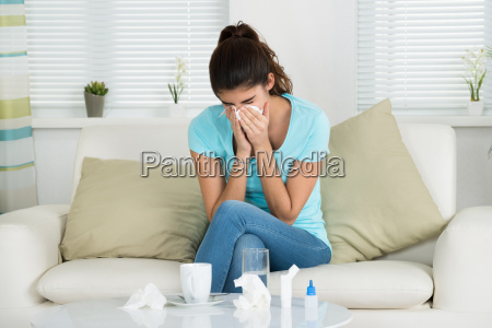 woman blowing nose on sofa at