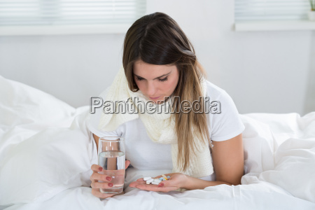 young woman holding medicine and glass