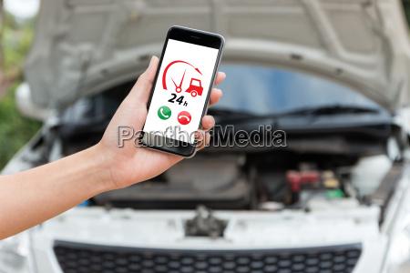 hand holding phone call emergency car