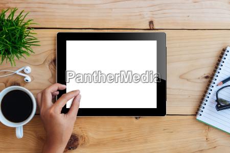 hand using mockup tablet on wood