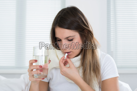 young woman taking pills and glass