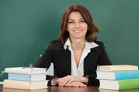 insegnante femminile seduto al banco dellaula