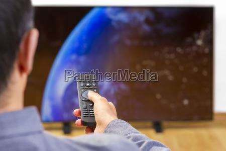uomo con telecomando che guarda la