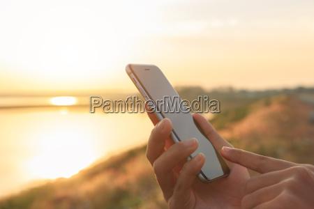 closeup hand using phone outdoor at