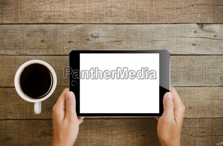 hand holding tablet on wood table