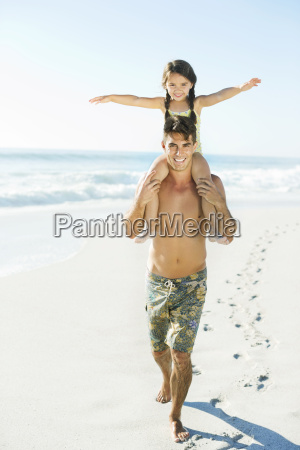 father carrying daughter on shoulders at