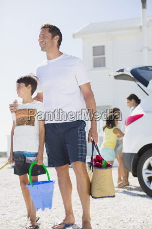 father and son holding beach gear