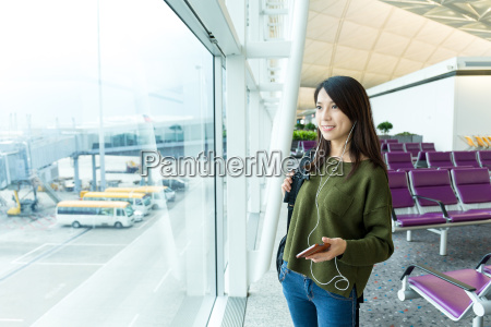 woman listen to music at airport