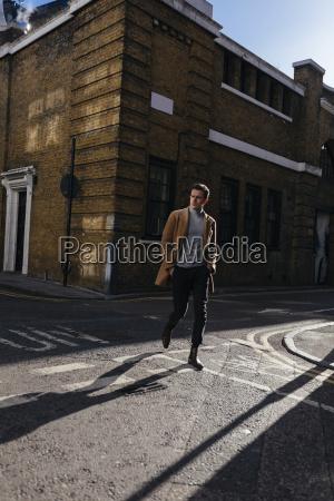 young man crossing urban street