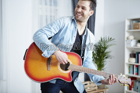 happy young man at home playing