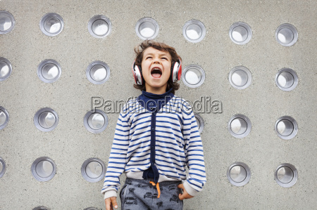 portrait of little boy singing while