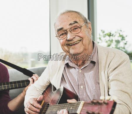 portrait of senior man playing guitar