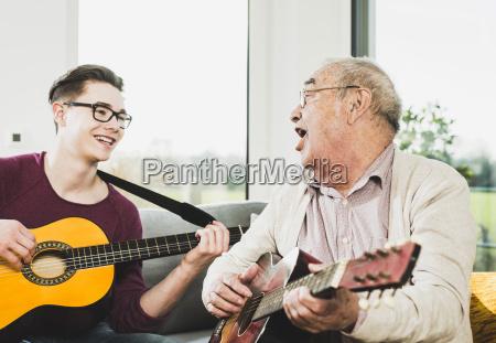 senior man singing and playing guitar